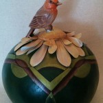 Sitting on top of a gourd by Debra Maerz